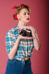Portrait of a girl dressed in vintage clothing holding old fashioned camera on the pink background. Pinup portrait
