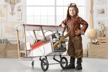 Boy in the image of a pilot playing with a plane