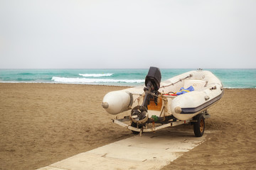 White inflatable boat stands on the sandy beach