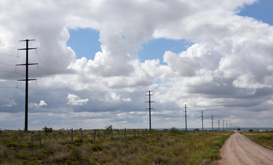 Row of electricity poles and high voltage power lines with blue sky and clouds in an empty rural landscape in Texas, USA