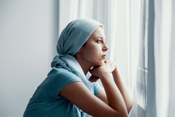 Thoughtful young girl suffering from bone cancer, wearing blue headscarf and looking through the window in hospital after surgery