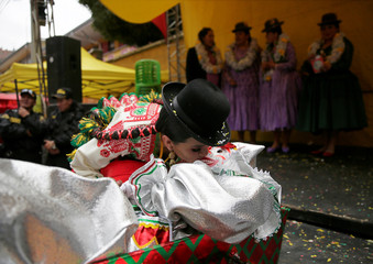 A Cholita (Andean woman) kisses a man dressed as Pepino, a carnival character to revive him as part of a ceremony to kick off carnival season in La Paz