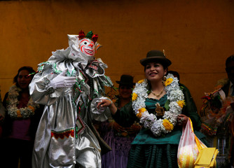 A man dressed as Pepino, a carnival character dances with a Cholita (Andean woman) during a ceremony as carnival season kicks off in La Paz