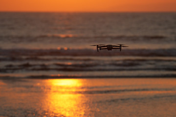 Dron flying above the sea during sunset