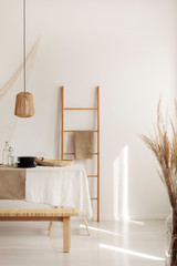 Wooden ladder with linen cloth on white wall of elegant natural dining room
