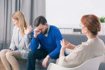Angry wife and sad husband during marriage psychotherapy with counselor