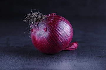 Red onions on a black table