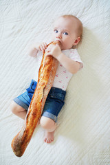 Six months old baby girl eating bread