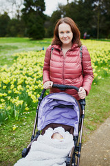 Happy young woman walking her little baby outdoors