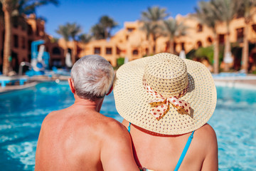 Senior couple relaxing by swimming pool. People enjoying vacation. Valentine's day