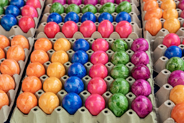Multicolored Easter eggs in the trays in rows close-up