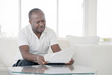 Man reads negative news in a letter at home on the couch. The shaken business manager of the african male received a notice of dismissal from the company, surprised. An agitated man without joy.