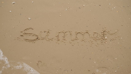 The inscription SUMMER is written on the sea sandy beach