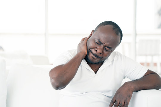 Tired neck. Man suffering from neck pain at home on couch. Males sense of fatigue, exhausted, stressed. African man massages her painful neck with her hands. The concept of body and health.