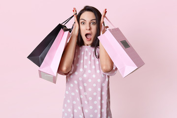 Shocked overwhelmed young pretty woman keeps jaw dropped, has no money for buying expensive thing, holds bags, goes shopping on weekend, isolated over rosy studio background, reacts on big sales