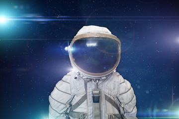 Retro cosmonaut or astronaut or spaceman with helmet on space with stars and blue light effects background, abstract science fiction concept