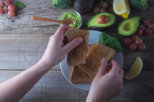 Avocado toast. Making sandwiches with avocado, guacamole healthy organic food. Woman hands cooking healthy food. Rustic wooden table.