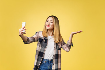 Pretty girl take a self portrait with her smart phone. Asian girl selfie, isolated on yellow background.