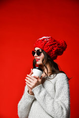 Close up portrait of a smiling young girl in hat holding take away coffee cup