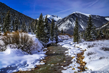 Mountain stream with fresh snow on sunny day