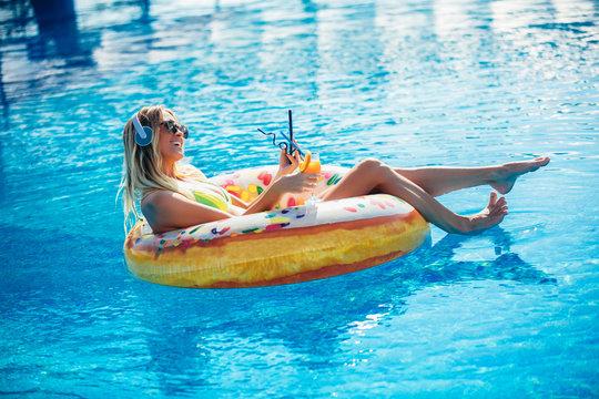 Summer Vacation. Enjoying suntan Woman in bikini on the inflatable mattress in the swimming pool using digital tablet