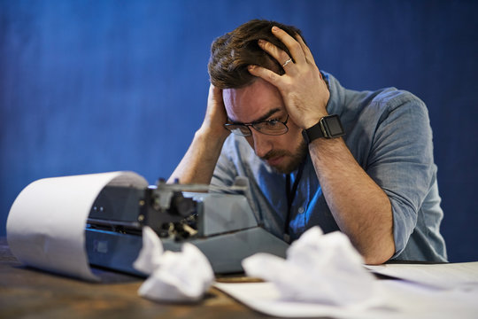 Portrait of frustrated bearded man struggling with writers block over typewriter