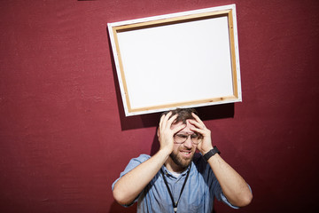 Portrait of man hit by picture frame standing against red wall shot with flash