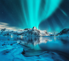 Aurora borealis over snowy mountains, frozen sea coast, reflection in water at night. Lofoten islands, Norway. Northern lights. Winter landscape with polar lights, ice in water. Starry sky with aurora