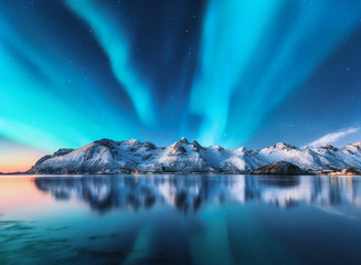 Northern lights and snow covered mountains in Lofoten islands, Norway. Aurora borealis. Starry sky with polar lights and snowy rocks reflected in water. Night winter landscape with aurora, sea. Nature