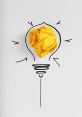 Composition with crumpled paper ball and drawing of lamp bulb on white background, top view. Creative concept