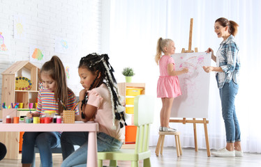 Female teacher with child near easel at painting lesson indoors
