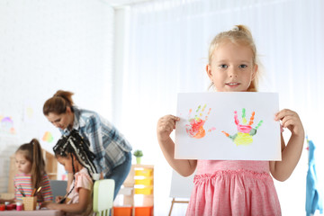 Cute little child showing sheet of paper with colorful hand prints indoors. Painting lesson