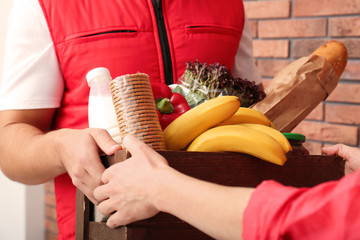 Male courier delivering food to client indoors, closeup