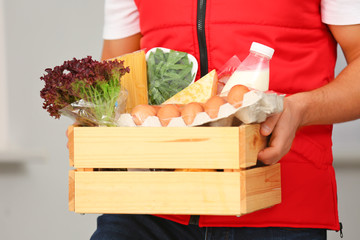 Male courier holding wooden crate with products on light background, closeup. Food delivery service