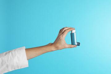 Female doctor holding asthma inhaler on color background, closeup. Medical object