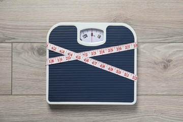 Scales and measuring tape on wooden background, top view. Weight loss