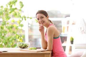 Young woman in fitness clothes preparing healthy breakfast at home