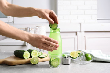 Young woman putting fresh cucumber slices into sports bottle on table. Space for text