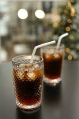 Glasses of cold cola on table against blurred background