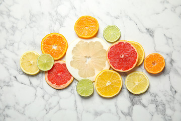 Different citrus fruits on marble background, top view