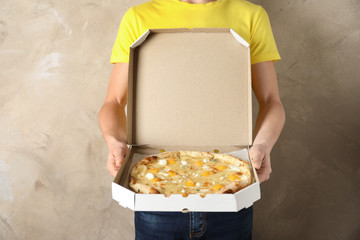 Young man with opened pizza box on color background. Food delivery service