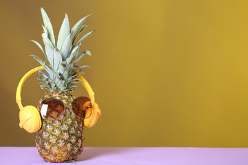 Pineapple with headphones and sunglasses on table against color background. Space for text