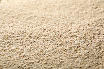Sesame flour as background, closeup. Organic product