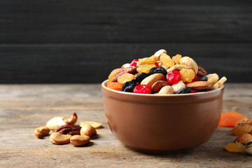 Bowl with different dried fruits and nuts on table. Space for text