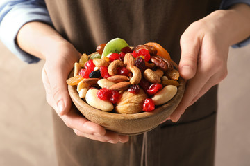 Young woman holding bowl with different dried fruits and nuts, closeup