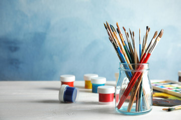 Glass jar with brushes and paints on table against color background. Space for text