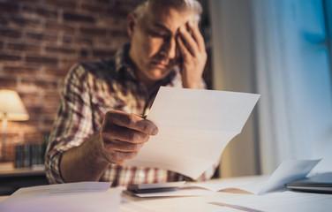Desperate man checking his domestic bills at home