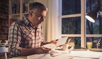 Shocked man checking bills at home