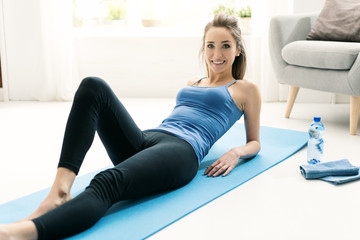 Happy woman exercising at home and relaxing