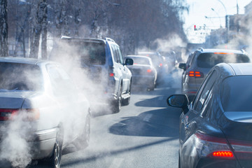 pollution from the exhaust of cars in the city in the winter. Smoke from cars on a cold winter day Fotobehang